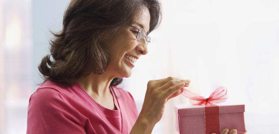 Hispanic woman opening gift